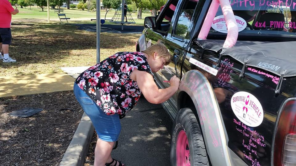 woman signing SAM the Survivor vehicle